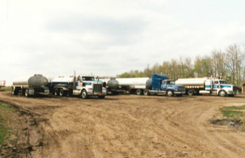 Old image of multiple water transport trucks lined up on a gravel road