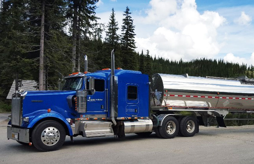 Liquids in Motion blue and silver bulk liquid hauling truck on paved road in front of trees