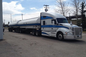 Liquids in Motion white and blue bulk liquid hauling truck on paved road.