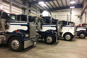 Four white and blue Liquids in Motion water hauling trucks parked in shop