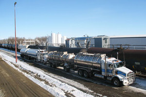 Two white and blue Liquids in Motion bulk liquid moving trucks parked beside a train