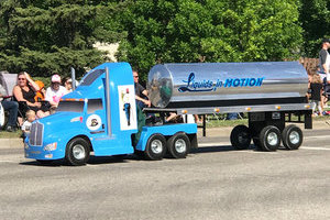 Small version of a liquids in motions water hauling truck taking part in Leduc Black Gold Pro Rodeo's parade